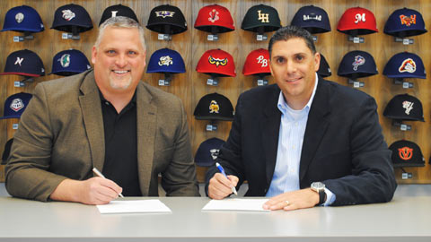 Ump-Attire.com CEO Jim Kirk (left) and PBUC executive director Justin Klemm sign their agreement.